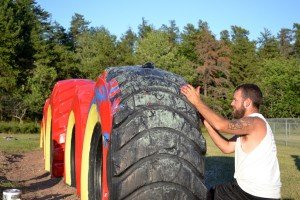 A Volunteer Repaints the Tires on the Playground of Gilbert Elementary