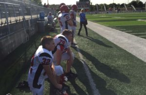 A couple of Marquette Redmen take a knee for a downed player.