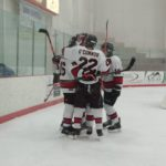The Marquette Redmen celebrate a goal behind the Eagles' net.