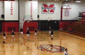 The Marquette Redettes warm up for their game against the Gladstone Braves