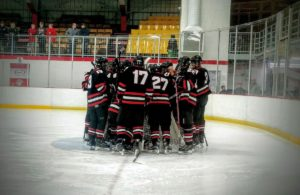 The Redmen surround their goaltender.