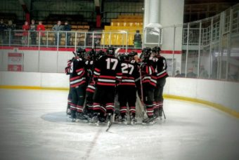 The Redmen surround their goaltender.