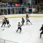 Marquette's Tanner Phillips (#10) skates with the puck in his own zone.