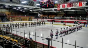 The Redmen and the Flivvers line up for the national anthem