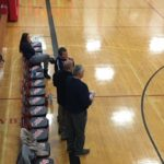 Marquette coach Ben Smith talks with Westwood coach Kurt Corcoran before the game