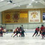 Both teams skate after puck.