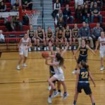 Reaching around the Negaunee Miners defense for an attempted basket.