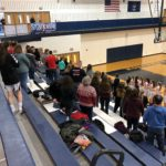 The Redettes stand for the National Anthem.