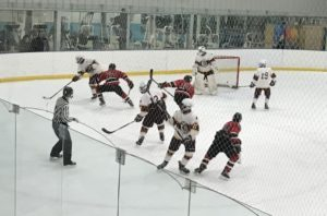 The Davison Cardinals attempt to break the puck out of their zone while battling the Marquette Redmen