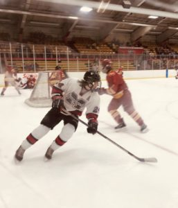The Marquette Redmen work the puck below the red line in the Bulldogs' zone