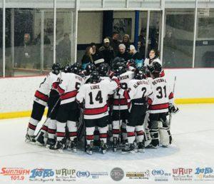 The Marquette Redmen celebrate around their net