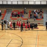 The Redettes line up at their bench.