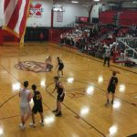 A Redmen takes on a Trojan as he makes his way down the court.