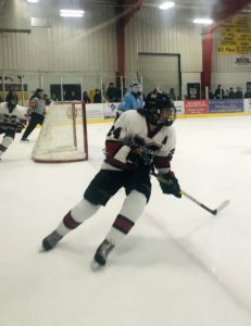 The Redmen skate hard for a puck in the corner