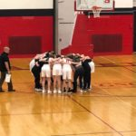 The Redettes huddle up before their match-up against the TC West Titans.