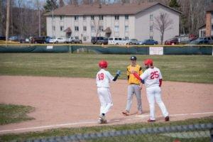 A Marquette Redmen player reaches first base on a walk